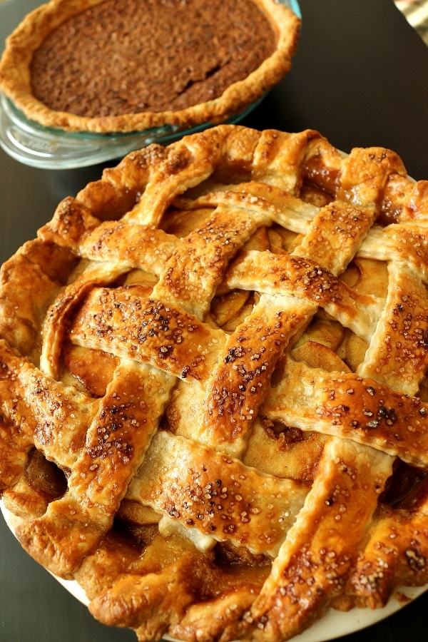 closeup of a lattice topped pie with a pecan pie in the background
