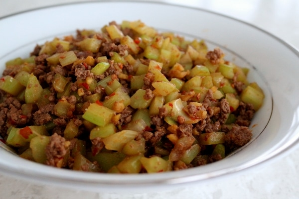 side view of stir-fried ground beef with celery in a white bowl