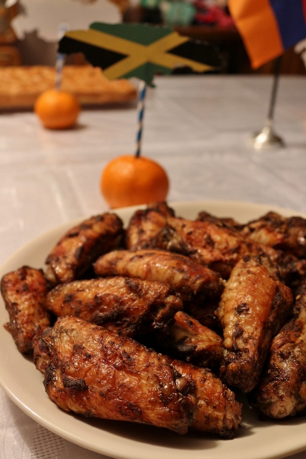 a platter of Jamaican jerk chicken wings with a Jamaican flag behind it