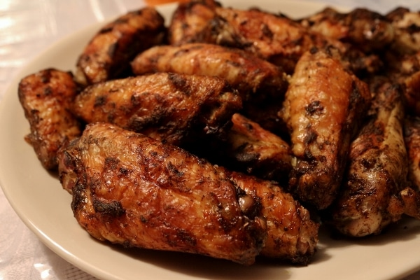 closeup side view of a platter of roasted jerk chicken wings
