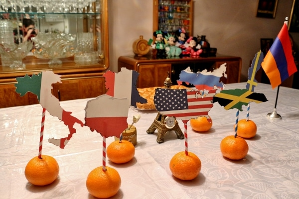 oranges with country shaped flags sticking out of their tops decorating a table