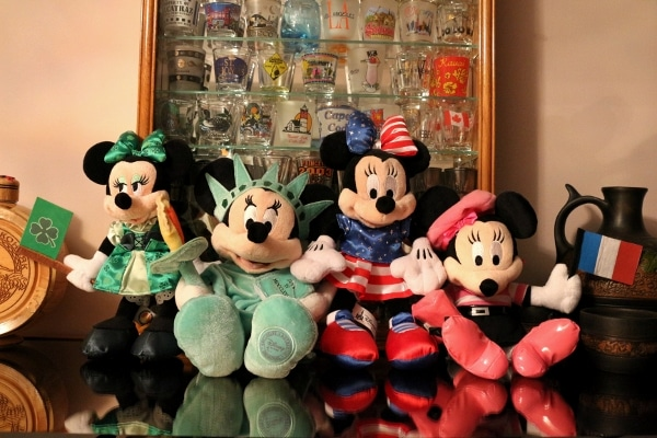 A bunch of stuffed Minnie Mouse dolls in different outfits