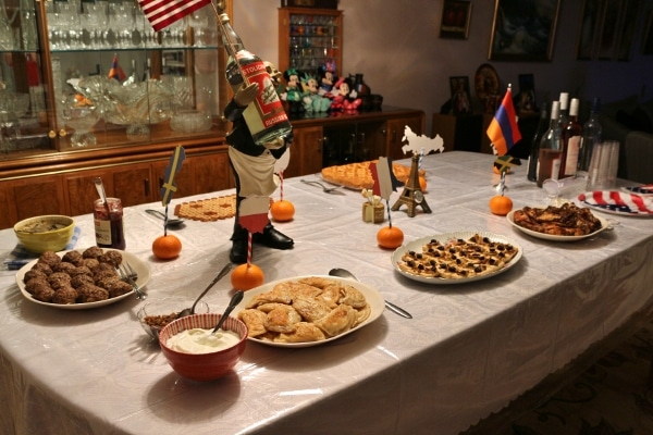 a wide view of a dining table topped with platters of food and various country flags