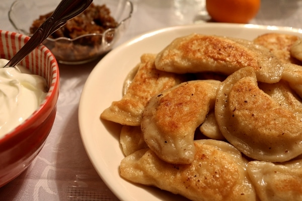 A closeup of a platter of pierogies with bowls of sour cream and caramelized onions