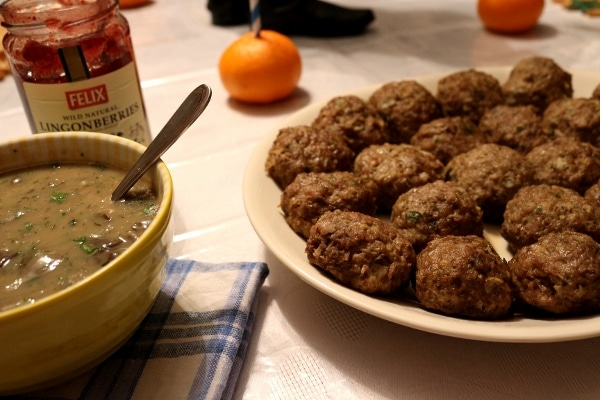 side view of a platter of Swedish meatballs with a yellow bowl of gravy