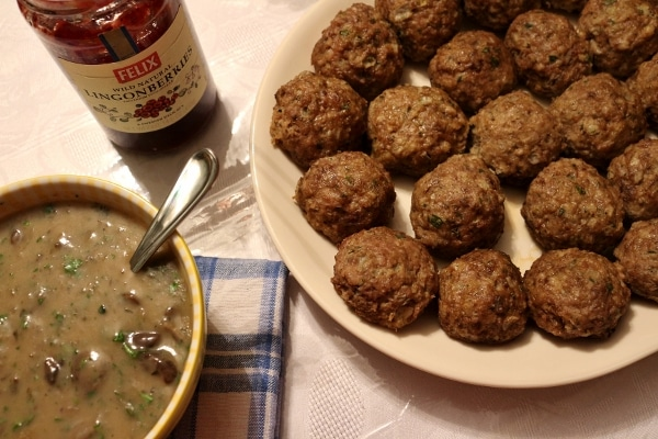 overhead closeup of a platter of meatballs and a bowl of gravy