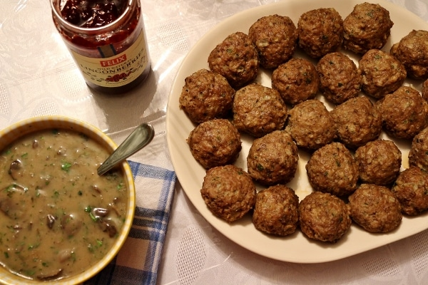 overhead view of a platter of meatballs, a bowl of gravy, and a jar of jam