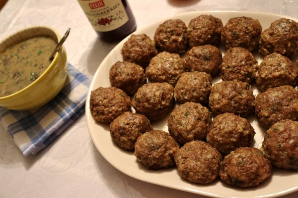 an oval platter of Swedish meatballs with a bowl of gravy to the side