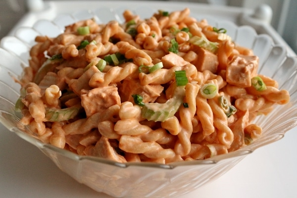 a glass serving bowl filled with buffalo chicken pasta salad topped with scallions