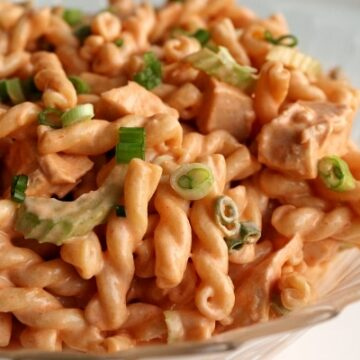 pasta salad made with gemelli pasta, chicken, and celery with an orange colored dressing