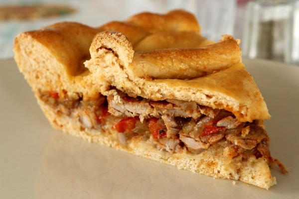 a slice of savory pie with meat and pepper filling on a plate