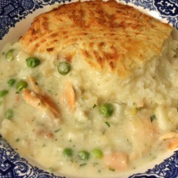 Irish fish pie with crusty mashed potato topping in a wide bowl with a blue edge