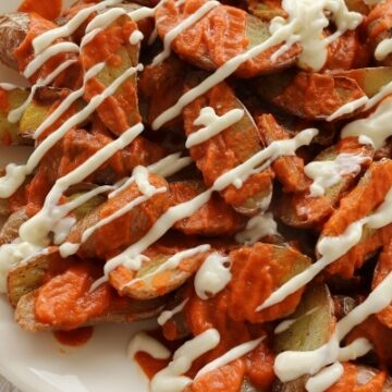overhead view of a platter of potato pieces topped with red and white sauces