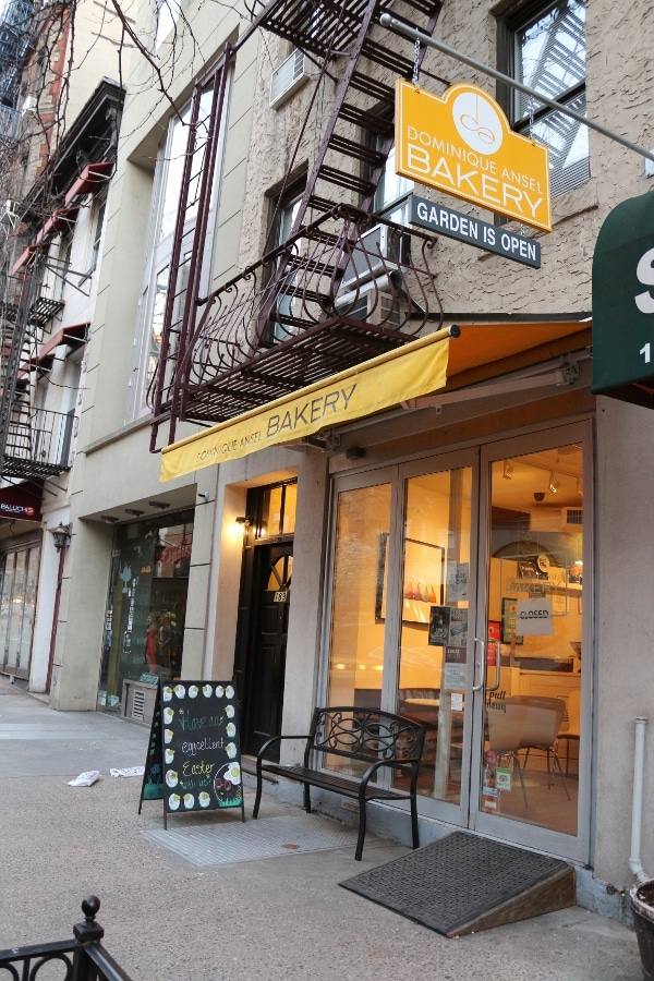 exterior of a bakery with yellow awning and a blackboard sign in front