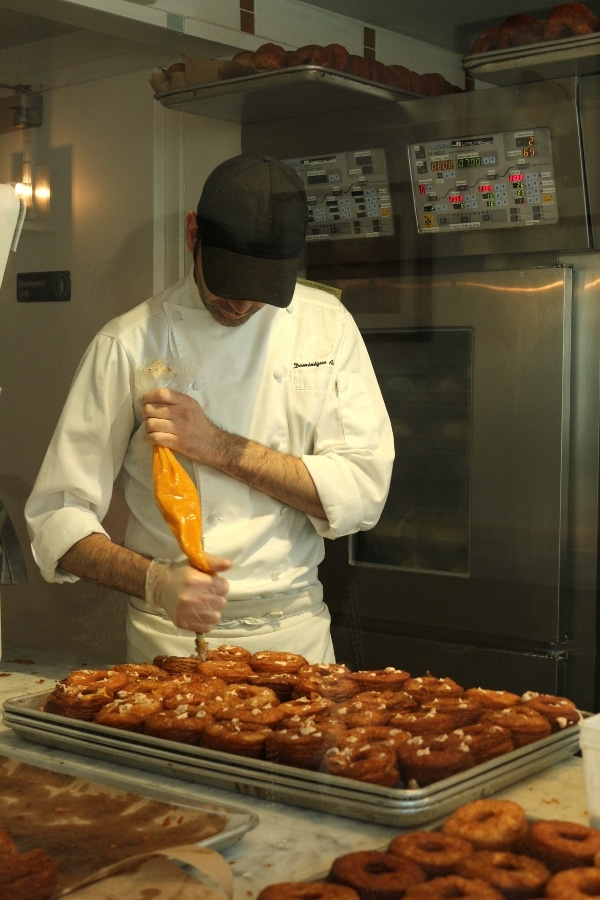 A man piping filling into doughnuts on a tray