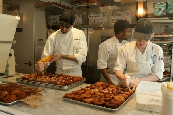 a group of people working in a bakery to prepare desserts