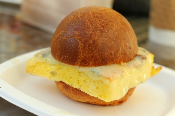 closeup of a breakfast sandwich on a golden bun with a square piece of egg inside