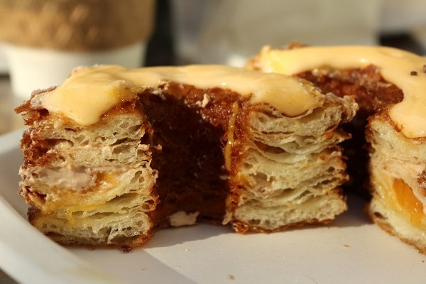 A closeup of a cross section of a flaky Cronut with layers of pasty