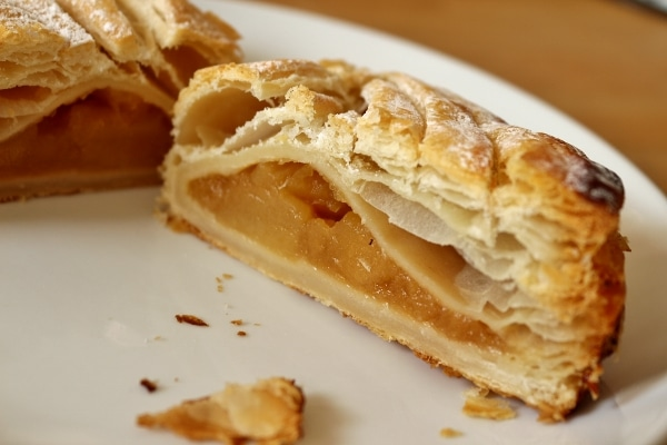 a cross section of an apple turnover on a white plate showing off the filling