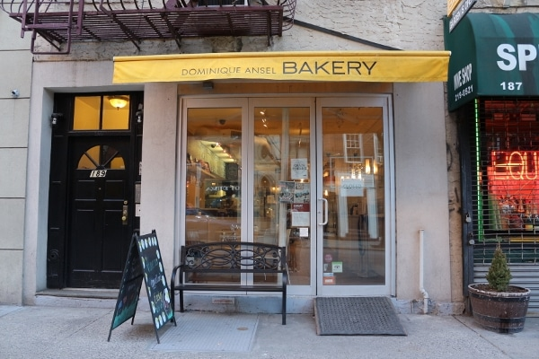 exterior of Dominique Ansel Bakery with a yellow awning over the storefront