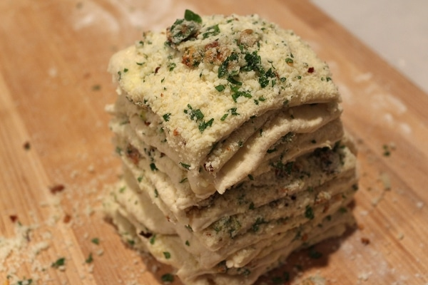 a stack of dough squares with grated cheese and herbs on a wooden surface