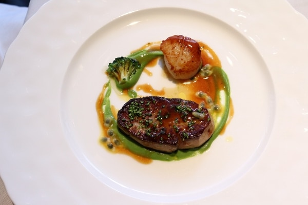 seared meat next to a scallop with a circle of green sauce on a white plate