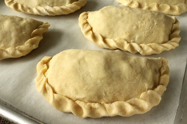 a closeup of unbaked empanadas with crimped edges on a parchment paper covered baking sheet