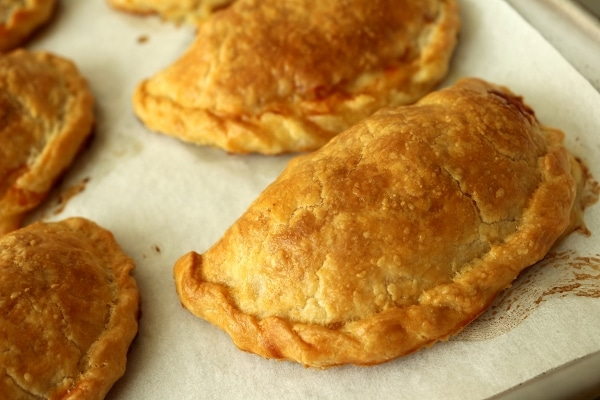 golden brown baked empanadas on a parchment paper covered baking sheet