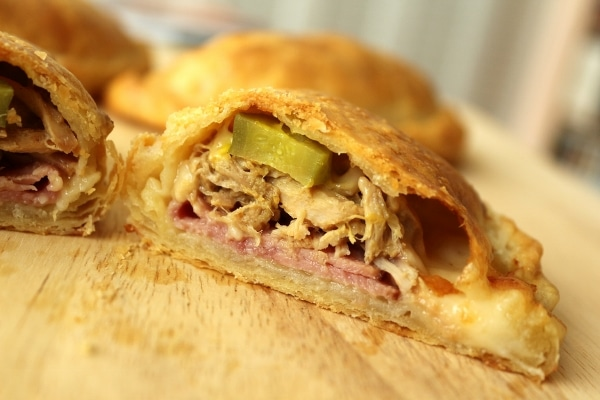 A closeup of a cross section of an empanada filled with ham, roasted pork, and pickles
