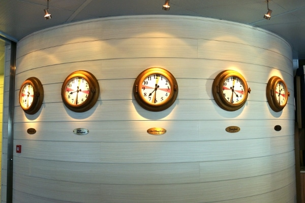 a row of clocks on a curved white wall