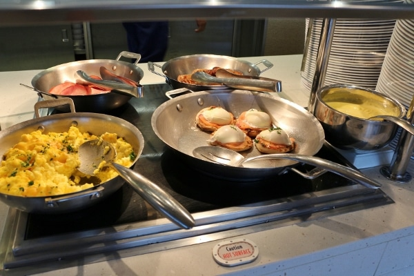scrambled eggs and eggs benedict in metal pans on a buffet line
