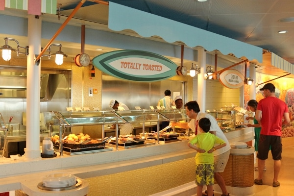 a closeup of a beach themed buffet with a surf board shaped sign hanging overhead