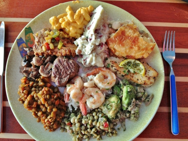 A plate of food including shrimp, fish, and lentils from a buffet