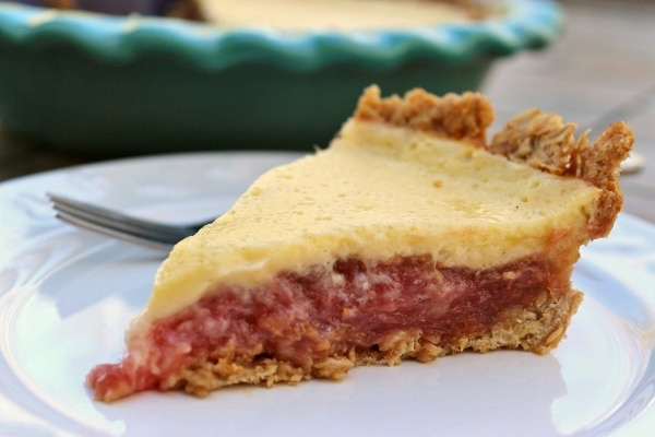a close up of a slice of rhubarb custard pie on a white plate