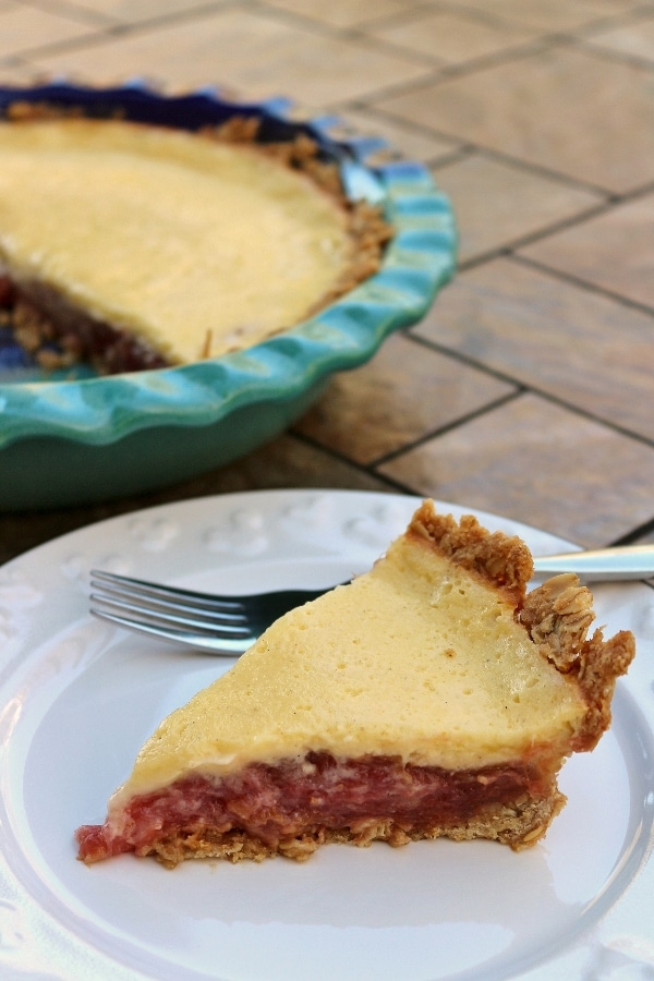 a slice of rhubarb custard pie with a blue pie plate in the background