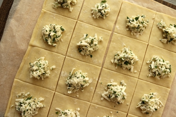 Assembling cheese boreks: puff pastry cut into squares, topped with grated feta cheese and parsley
