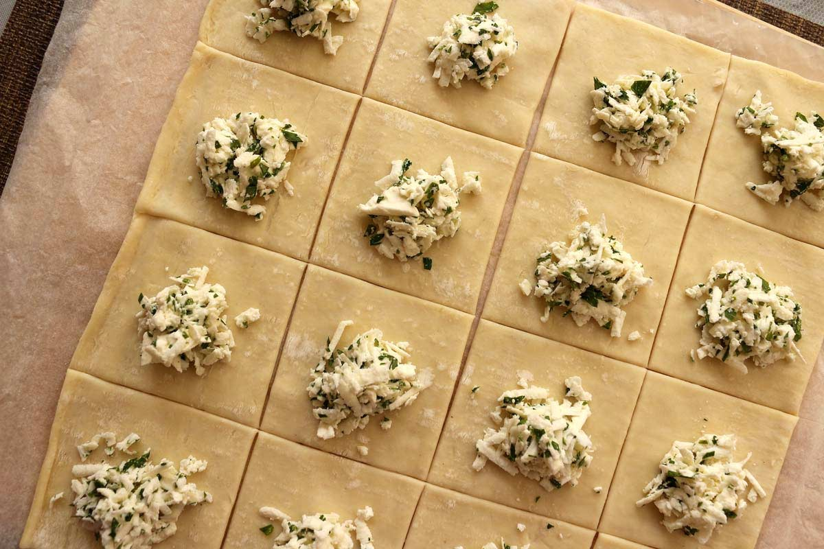 Assembling cheese boreks: puff pastry cut into squares, topped with grated feta cheese and parsley.