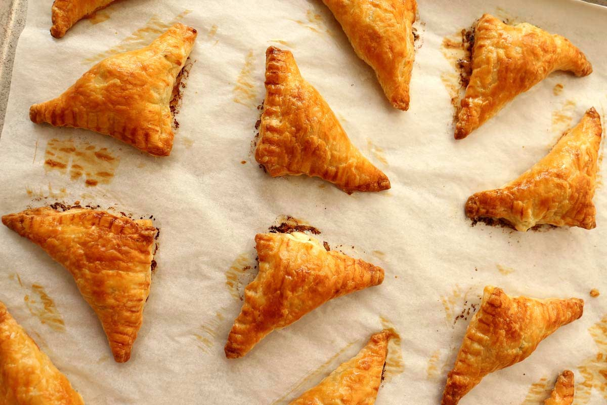 Golden brown cheese borek puff pastry triangles on a baking sheet.