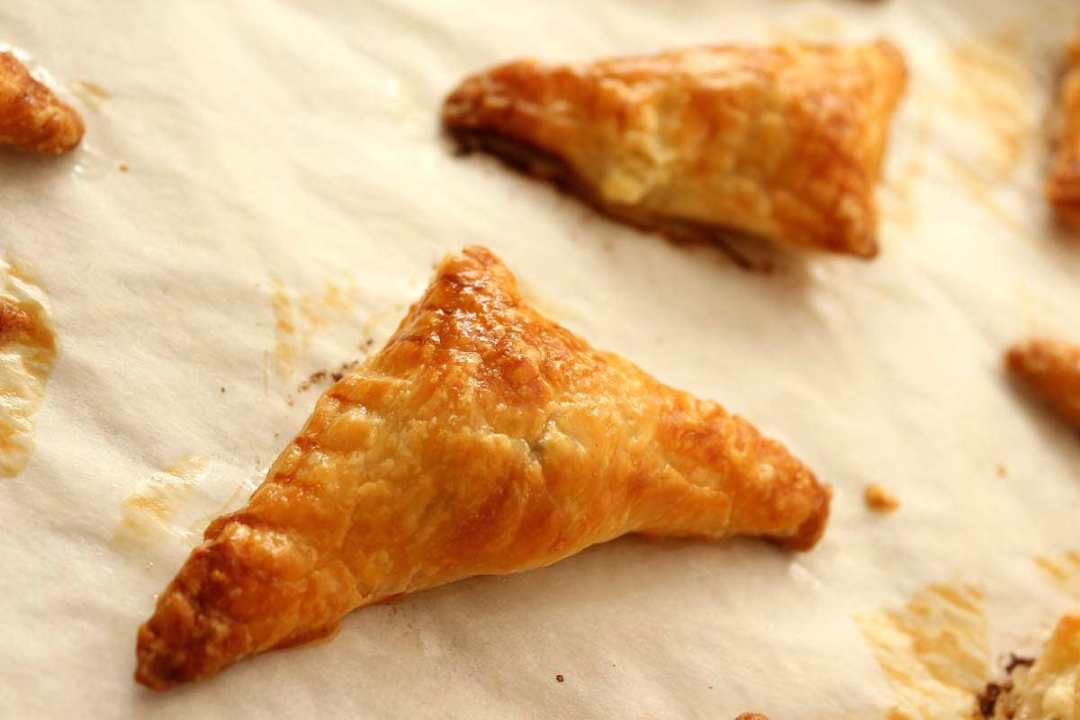 Closeup of a golden brown puff pastry triangle on a baking sheet.