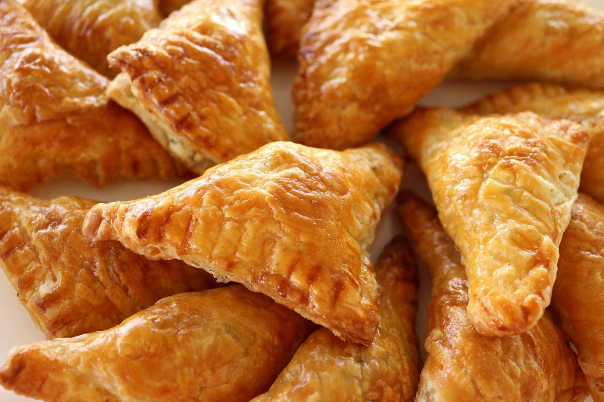 A platter of crispy, golden puff pastry triangles.