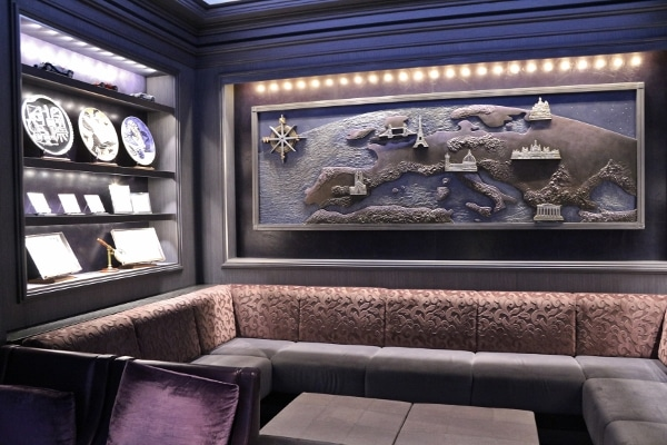 a corner area in a bar with a map hanging over a sofa