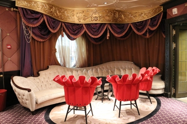 a lounge area with frilly red chairs and a long white couch