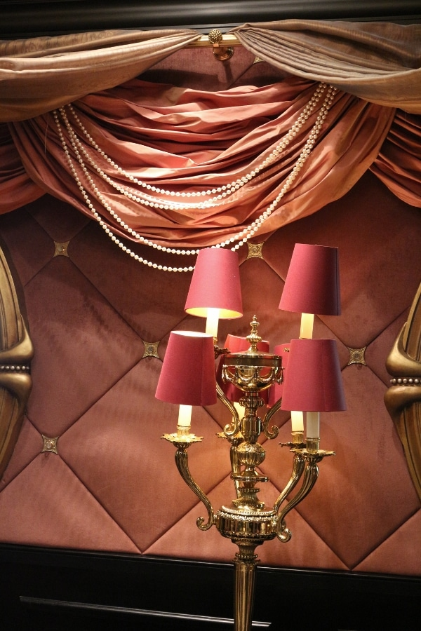 A lamp on a table with a pink tufted wall behind it