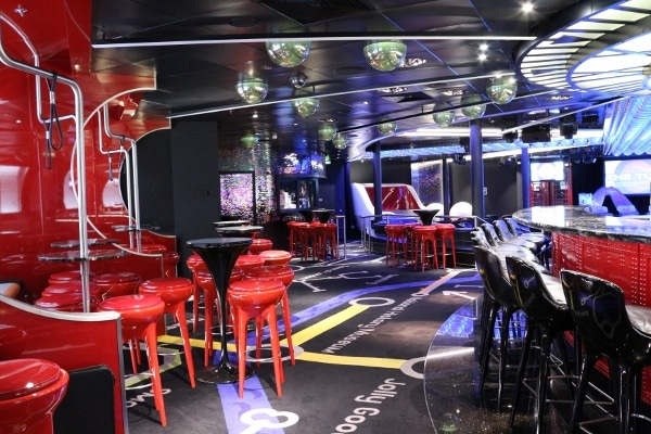 interior of a nightclub with bright red stools and carpeting that is a London Tube map