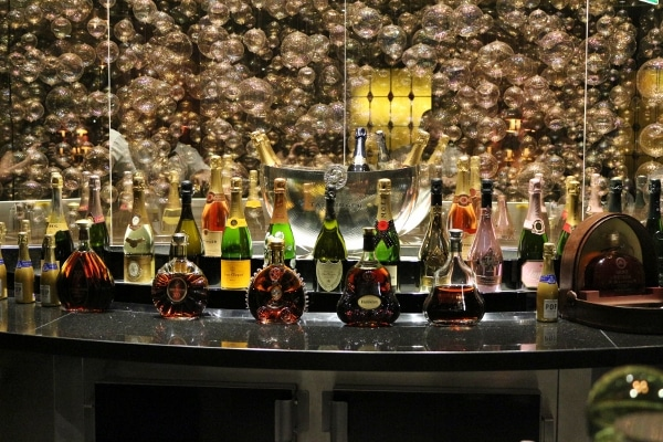 bottles of alcohol on a bar with images of bubbles on the wall behind them