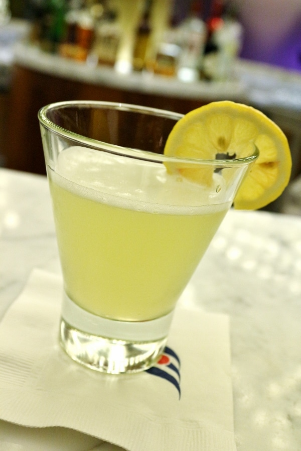 A drink in a short glass with a lemon slice garnish