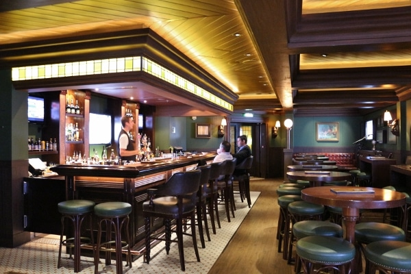 interior of an Irish pub with dark green and wood decor and a long bar