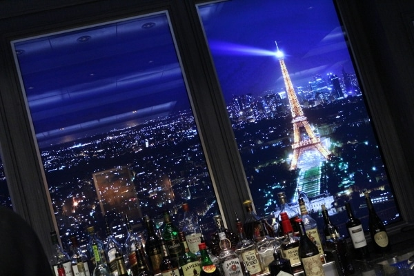 an image of the Eiffel Tower behind a bar stocked with bottles of alcohol