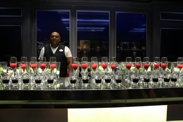 rows of glasses of drinks lined up on a bar with a man standing behind it