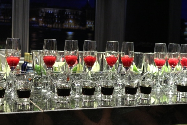 a closeup of glasses of drinks lined up on a bar